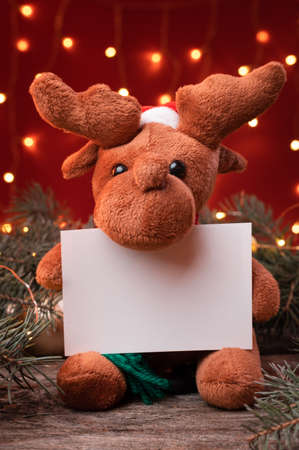 Cute reindeer toy in santa hat holding a white writeable card, sheet of paper in a Christmas scenario.