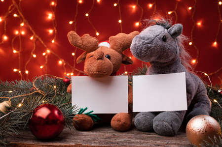 Cute reindeer in santa hat and horse toys holding a white writeable card, sheet of paper in a Christmas scenario.