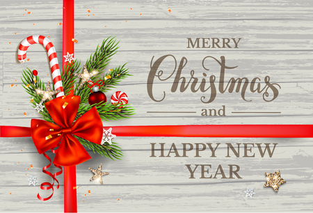 Festive Christmas fir tree branches and ribbon on wood background. Natural design elements. Festive background with festive decorations