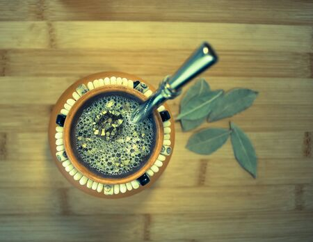 mate infusion: Yerba mate infusion in clay mug with bombilla, high angle view