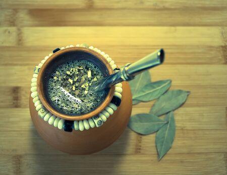 yerba mate: Taza de la arcilla con la infusión caliente de la yerba mate y bombilla, vista de ángulo alto, fondo de madera. Foto de archivo
