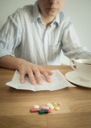doctors with pills: Sad young man in white shirt reading drugs leaflet with his morning coffee. Handful of colored pills in the foreground. Vertical.