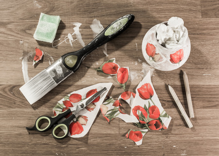 Decoupage workshop: scissors, brush, paper, sponge and pencils on wooden table. Stock Photo