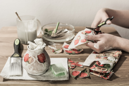 decoupage: Decoupage: hands of hobbyist cutting paper flowers. Decoupage tools on a table.