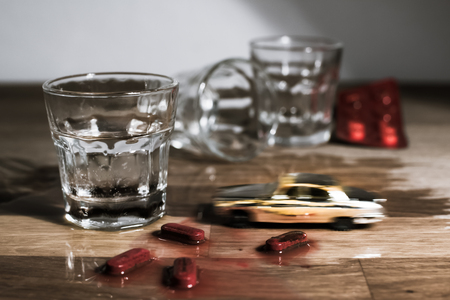 inebriated: Drunk driving metaphor - toy car crashing into shot of vodka; melting red pills pretending accident victims.