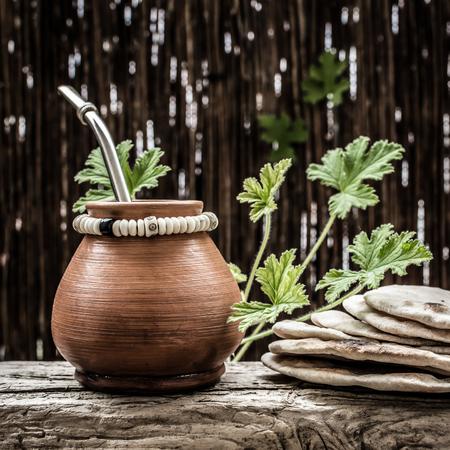 yerba mate: matero arcilla con la infusi�n de yerba mate y bombilla; algunas tortillas de trigo hechas en casa en el lado.