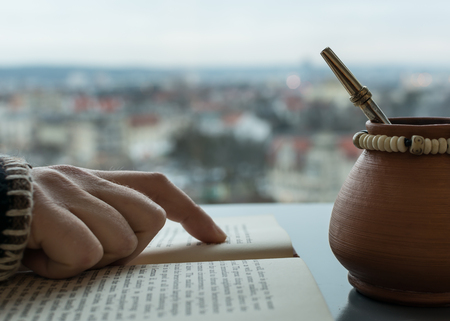 yerba mate: Hand of a person reading a book with yerba mate mug and blurry city view in the background.