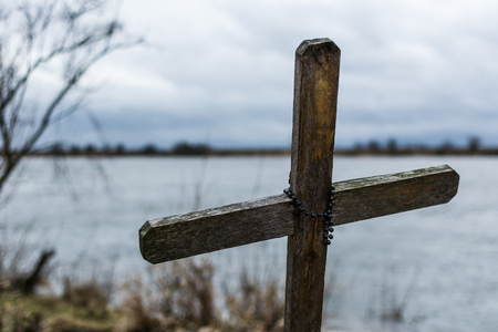 memorial cross: Old wooden cross with rosary - memorial of drown fisherman - standing on the shore of Vistula River in Kashubia region in Poland.