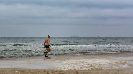 submerging: Sturdy sportsman warming up before submerging in freezing water on baltic beach. Gdansk, Poland, 12022017