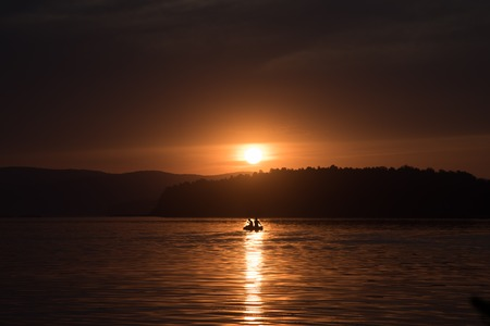 fisher: Silhouette of fisher and dog sitting in boat