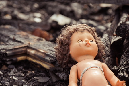Abandoned child's baby doll with blue eyes on parched desert dirt. Standard-Bild