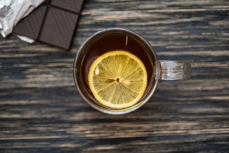 Cup of tea with lemon on the wooden table.
