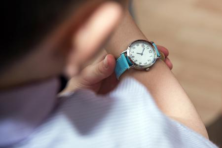 Boy looking at his wrist kid watch. 写真素材