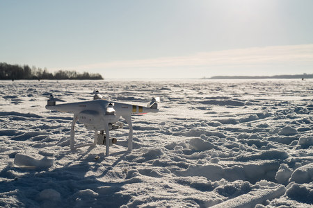 quad: White drone quad copter with flying in the blue sky.