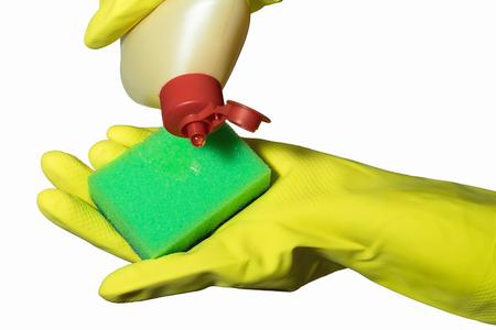 servicio domestico: Primer plano de la mano femenina en amarillo guante de goma protectora que sostiene una esponja de limpieza verde sobre fondo blanco Foto de archivo