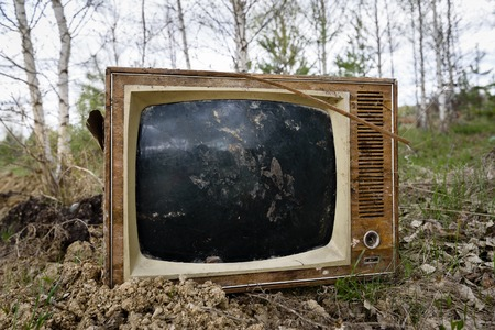 discarded: Old analog discarded television set in the forest. Stock Photo