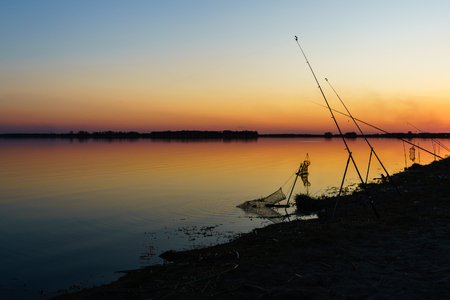jigging: spinning with reel and evening summer lake.