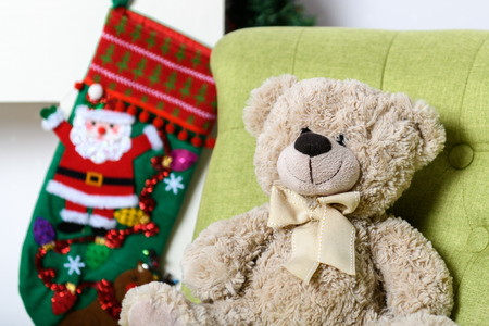 Interior room: Teddy bear in a chair under the Christmas tree