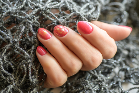 Woman with beautiful manicured red fingernails gracefully crossing her hands to display them to the viewer on a gray background in a fashion, glamour and beauty concept Stock Photo