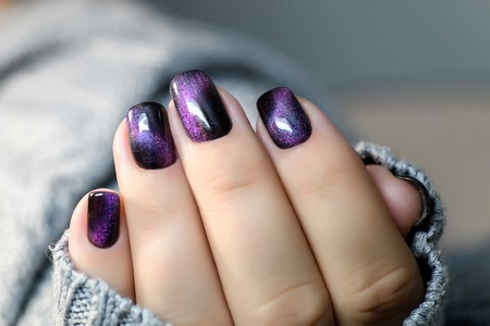 Beautiful nail polish in hand, purple nail art manicure, gray background.