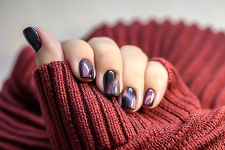 Beautiful nail polish in hand, purple nail art manicure, red background.