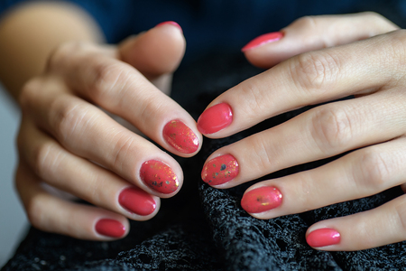Woman with beautiful manicured red fingernails gracefully crossing her hands to display them to the viewer on a gray background in a fashion, glamour and beauty concept.