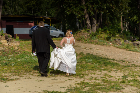 Bride and groom walking away in summer park outdoors