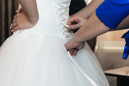 Closeup of bridesmaid tying bow on bride's dress.