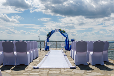 Wedding arch with empty chairs on the background of the lake.