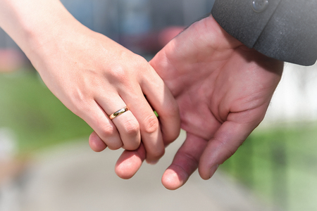 Closeup of bride and groom showing wedding rings touching hands. 免版税图像