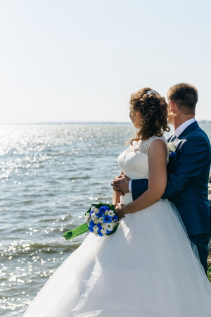 bride and groom standing in front of the lake and looking into the distance. Standard-Bild