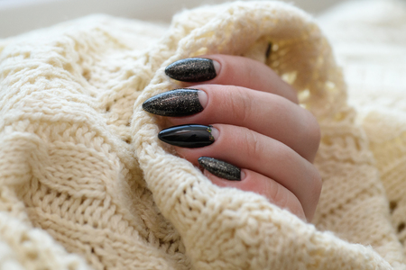 Beautiful winter manicure. Black lacquer with luster and white patterns of snow and frost. The white background is also with beautiful curled drawings