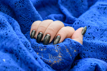 Beautiful winter manicure. Black lacquer with luster and white patterns of snow and frost. The blue background is also with beautiful curled drawings