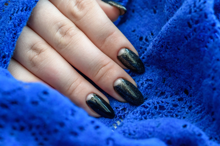 Beautiful winter manicure. Black lacquer with luster and white patterns of snow and frost. drawings