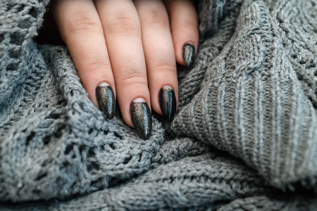 Beautiful winter manicure. Black lacquer with luster and white patterns of snow and frost. The gray background is also with beautiful curled drawings.
