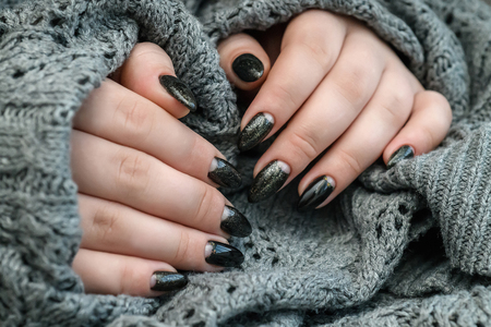 Beautiful winter manicure. Black lacquer with luster and white patterns of snow and frost.