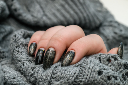 Beautiful winter manicure. Black lacquer with luster and white patterns of snow and frost. The gray background is also with beautiful curled drawings Standard-Bild