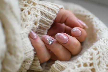 매니큐어. 아트 매니큐어. 현대적인 스타일 블루 매니큐어. 스타일 파스텔 컬러 핑크 화이트 손톱 양모 소재 슬리브 블라우스 격리 된 흰색 배경 벽을