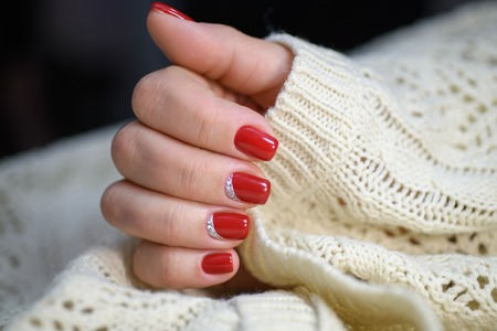 Hands with long artificial manicured nails colored with red nail polish.