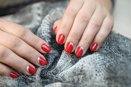 Hands with long artificial manicured nails colored with red nail polish Stock Photo