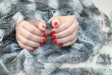 Hands with long artificial manicured nails colored with red nail polish Standard-Bild