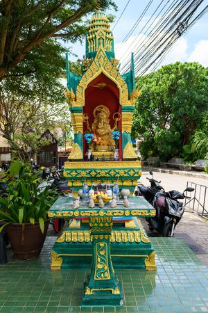 Abandoned yellow-green house of the spirit. House spirit style Thailand on the street under the trees. Standard-Bild