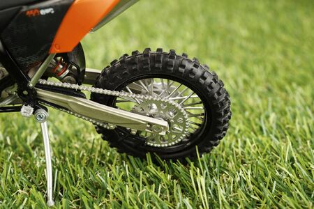 grassy field: closeup of artificial green grass with motorcycle model Stock Photo