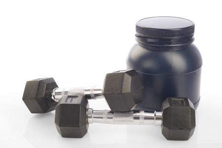 Isolated two dumbbells and protein powder bottle on white background photo