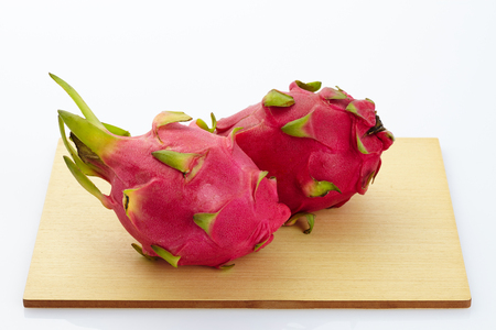 dragon fruit slicing on chop block in white background