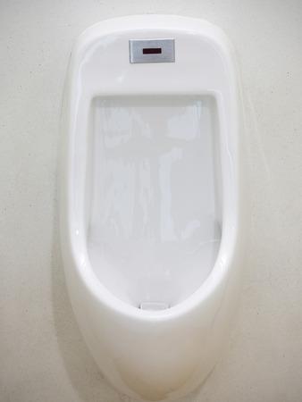 white porcelain urinals in public men toilets photo
