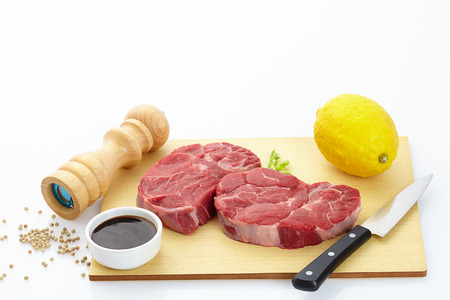 Fresh steak with spices on wooden background