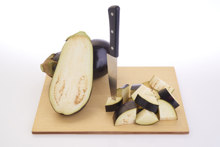 Cutting eggplants on wooden cutting board before cooking photo