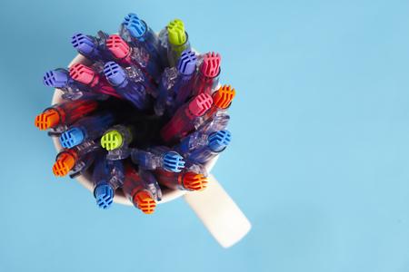 ball pens stationery: disparar diferentes tipos de plumas aisladas sobre fondo azul Foto de archivo
