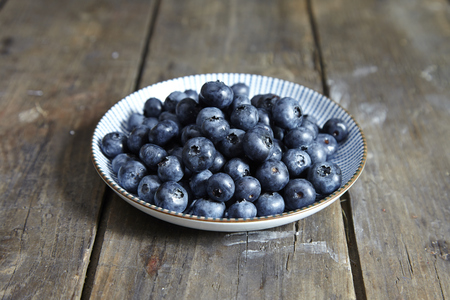 Blueberries in a white plate on wooden background
